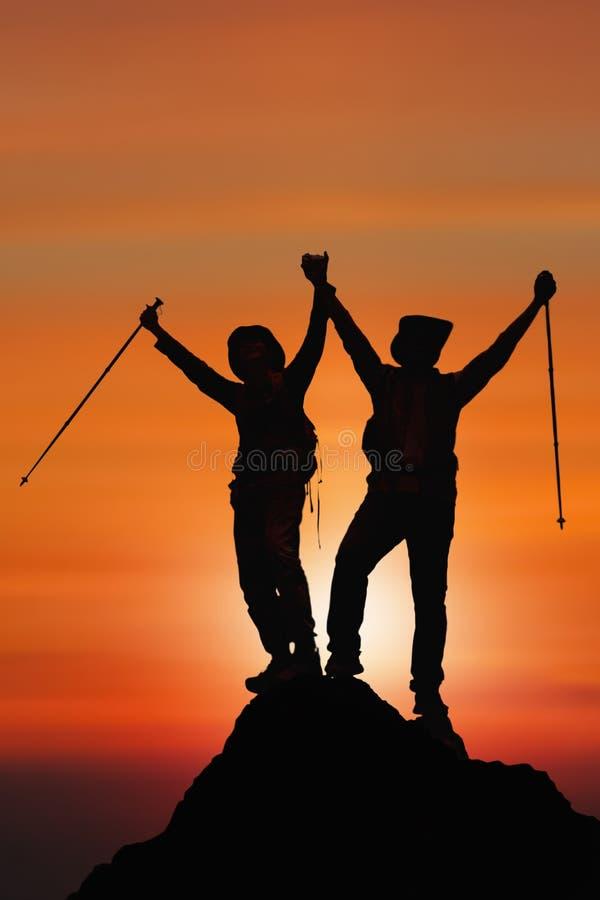 Silhouet van twee vrienden die voltooiing hebben die op berg aan de piek samen beklimmen stock afbeelding