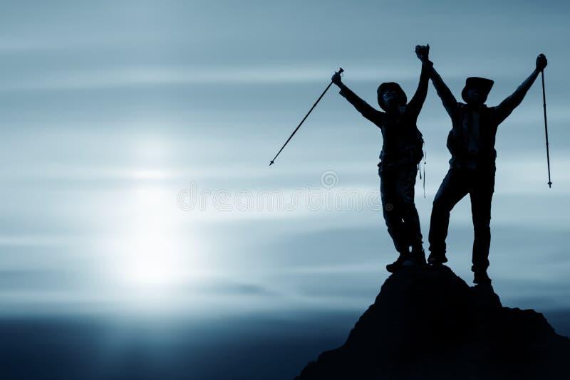 Silhouet van twee vrienden die voltooiing hebben die op berg aan de piek samen beklimmen stock foto