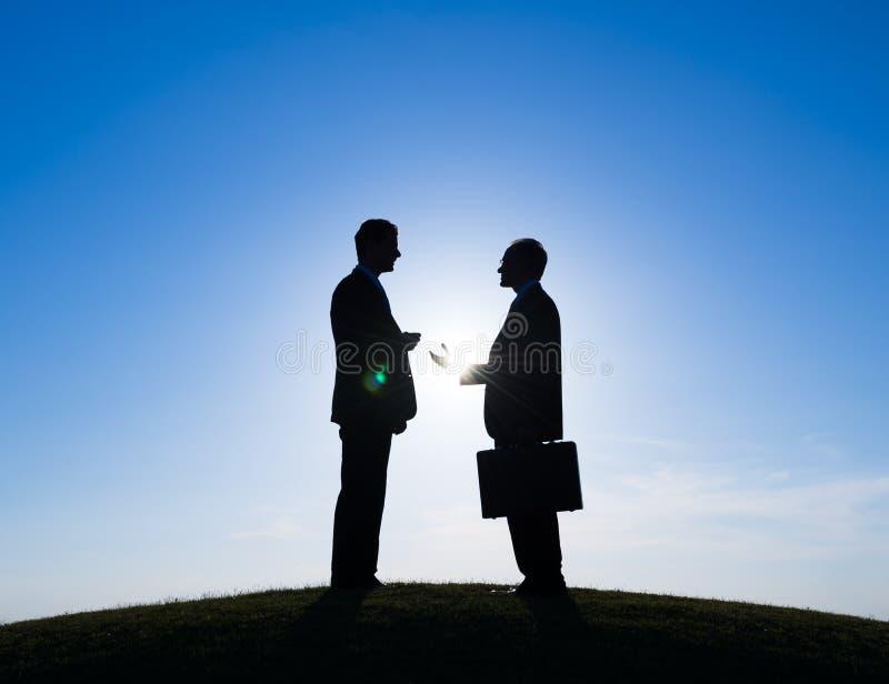 Silhouet van Twee Zakenlieden die samen spreken stock afbeelding