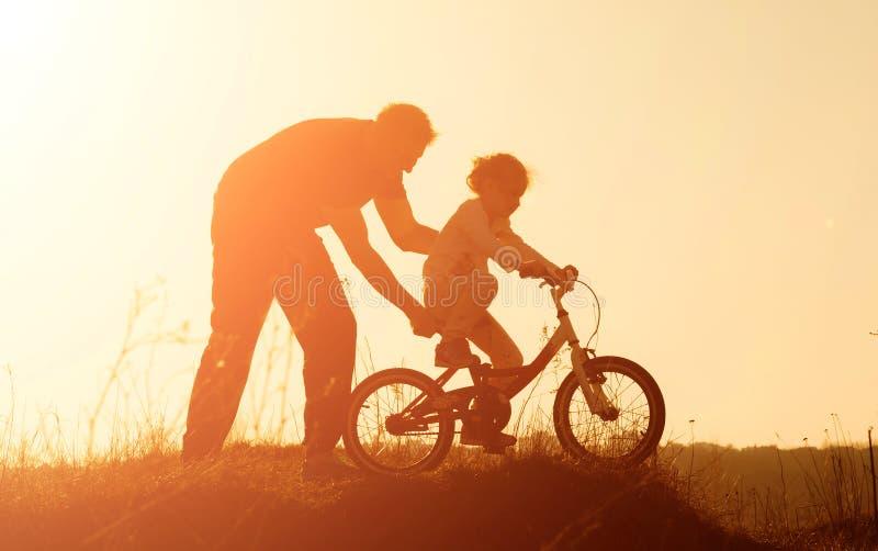 Silhouet van vader die zijn dochter onderwijzen om een fiets bij zonsondergang te berijden royalty-vrije stock foto's