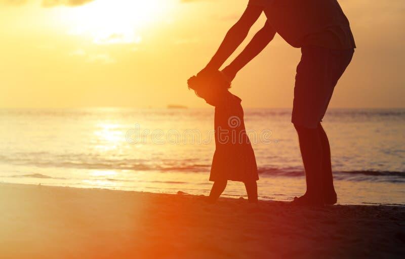 Silhouet van vader en dochter die leren te lopen stock foto's