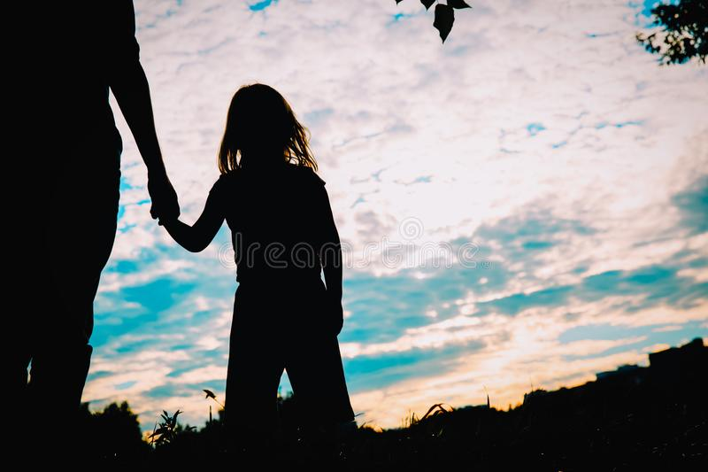 Silhouet van vader en dochterholdingshanden bij zonsondergang stock foto's