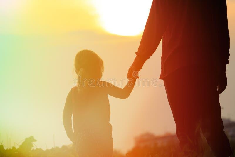 Silhouet van vader en dochterholdingshanden bij zonsondergang stock foto