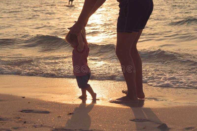 Silhouet van vader en weinig dochter die bij zonsondergangstrand leren te lopen Vrouwelijke zuigeling tien maanden oud Gelukkige  stock foto