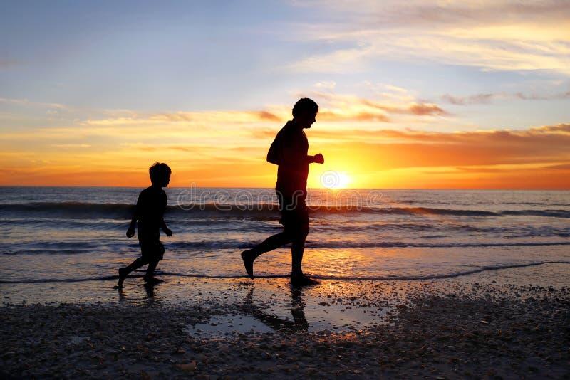 Silhouet van Vader en zijn Jonge Zoonsjogging op Strand samen bij Zonsondergang stock afbeeldingen