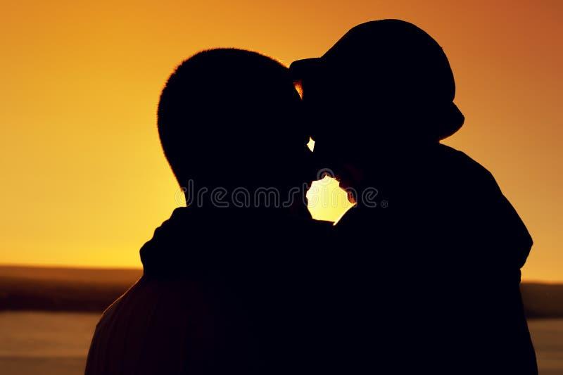 Silhouet van vader en zoon dichtbij overzees bij zonsondergang stock afbeeldingen