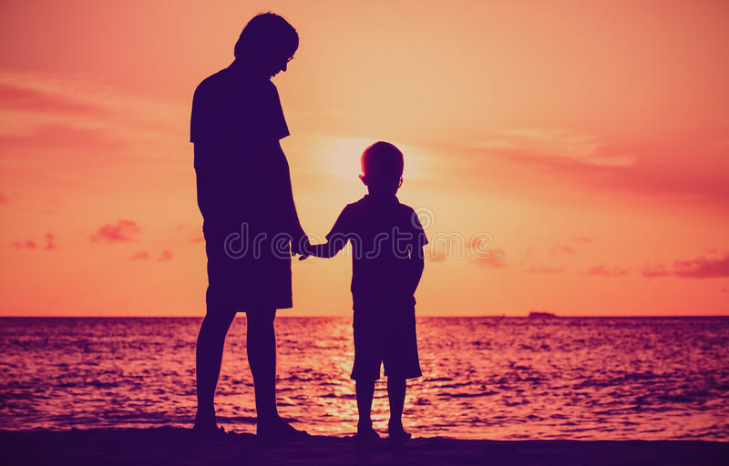 Silhouet van vader en zoonsholdingshanden bij zonsondergangoverzees royalty-vrije stock afbeeldingen