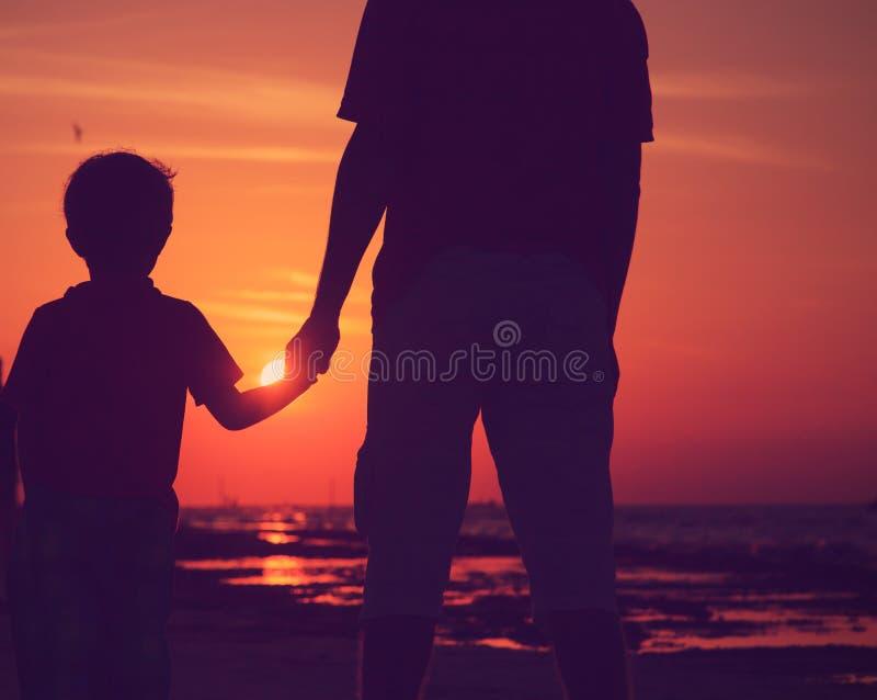 Silhouet van vader en zoonsholdingshanden bij zonsondergangoverzees stock foto's