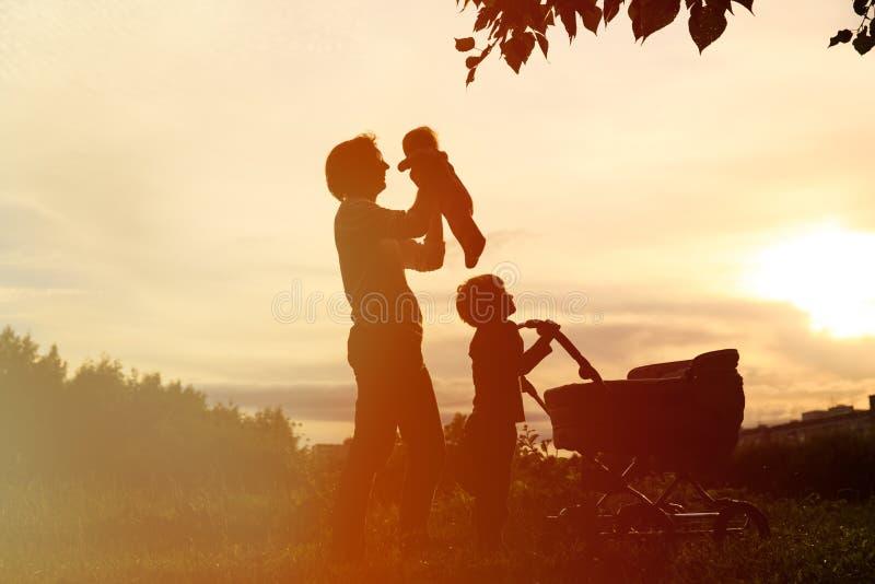 Silhouet van vader met twee jonge geitjes die bij zonsondergang, gelukkige familie lopen stock afbeelding