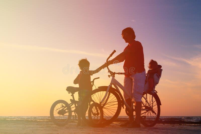 Silhouet van vader met twee jonge geitjes op fietsen royalty-vrije stock foto's