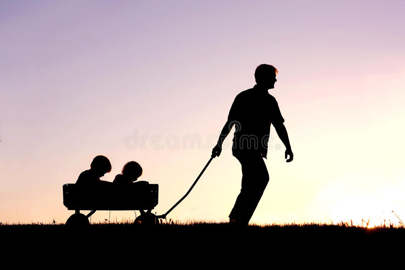 Silhouet van Vader Pulling Sons in Wagen bij Zonsondergang royalty-vrije stock afbeelding