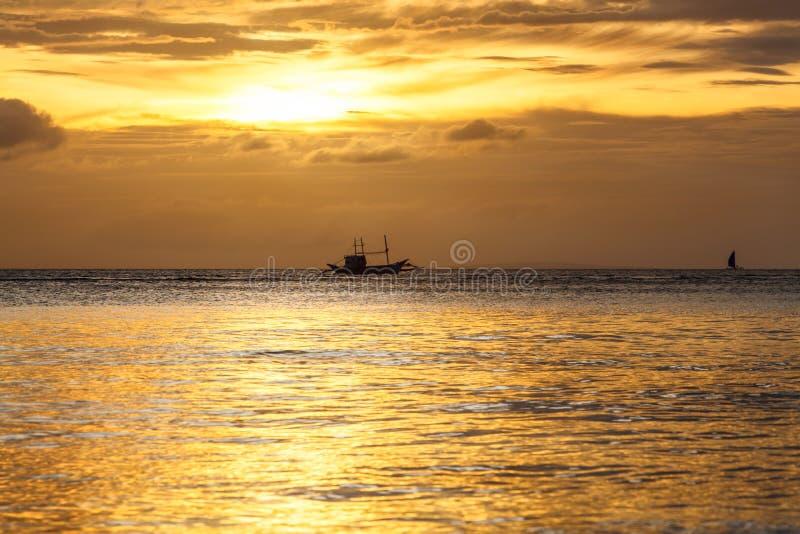 Silhouet van varende boot op horizon van tropische zonsondergangoverzees Filippijnen stock fotografie