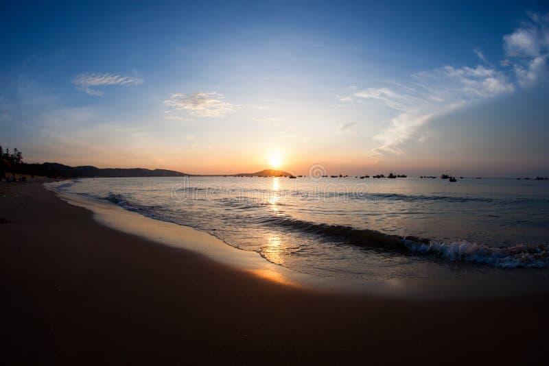 Silhouet van verscheidene kleine die vissersboten op zee van zandig strand worden gezien stock fotografie