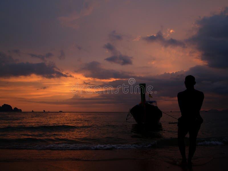 Silhouet van visser en traditionele Thaise longtailboot op zonsondergangachtergrond op strand in krabiprovincie royalty-vrije stock fotografie