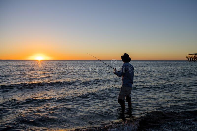 Silhouet van visser met hoed op het strand met vissenstaaf die zich bij het zeewater bevinden die bij zonsondergang met mooie ora royalty-vrije stock afbeeldingen
