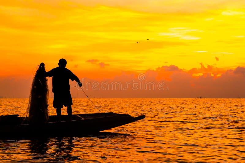 Silhouet van Vissers die in het meer in de zonsopgangtijd vissen royalty-vrije stock foto's
