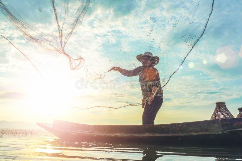 Silhouet van vissers die kippenren-als val gebruiken die vissen in meer met mooi landschap van de zonsopgang van de aardochtend v royalty-vrije stock fotografie