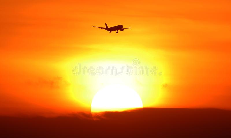 Silhouet van vliegtuig vertrekken die tijdens zonsondergang bij tropisch paradijs Bali Indonesië aankomen stock foto's