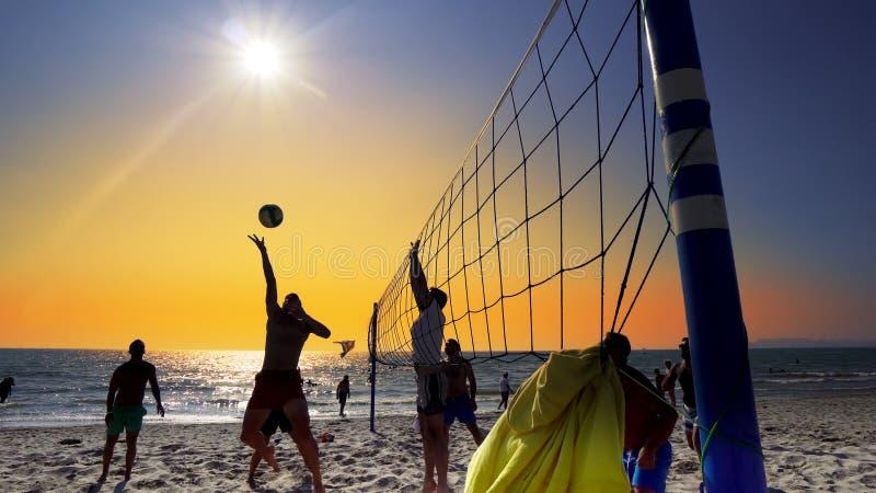 silhouet van volleyballspelers op het strand bij zonsondergang royalty-vrije stock fotografie