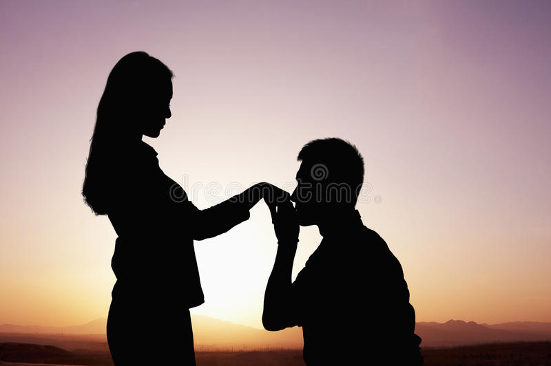 Silhouet van vriend die en zijn meisjeshand kussen bij zonsondergang knielen stock foto's