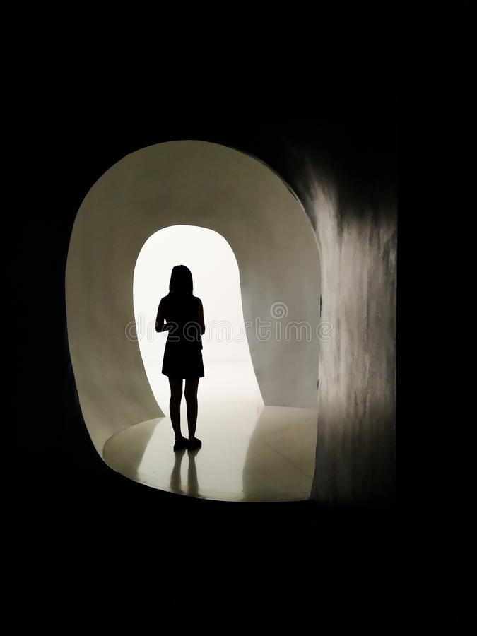 Silhouet van vrouw alleen voor lichte deur, bewegende geestelijke ziekte van de schaduwen in het licht royalty-vrije stock afbeelding