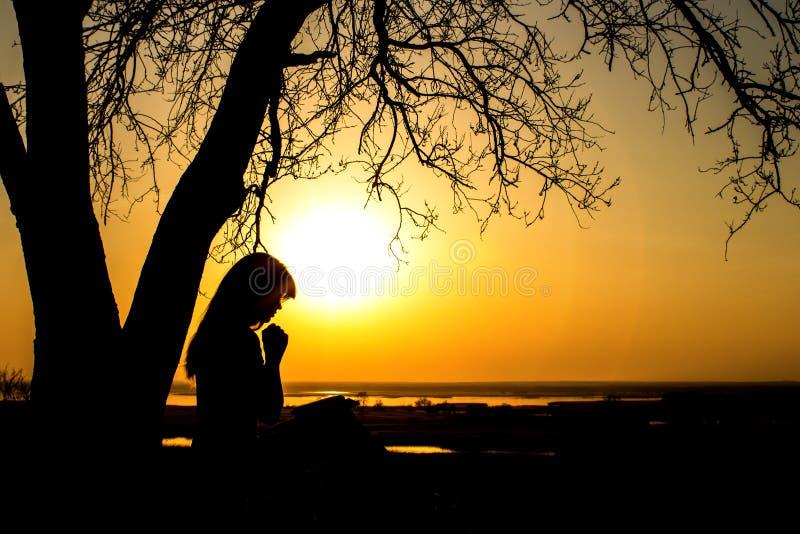 Silhouet van vrouw die aan God in de aard witth de Bijbel bidden bij zonsondergang, het concept godsdienst en spiritualiteit stock fotografie