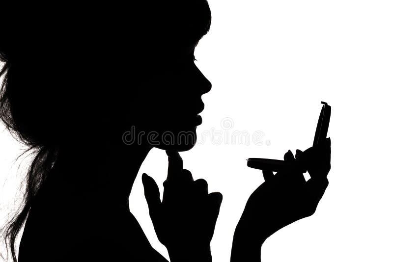 Silhouet van vrouw die bewonderen in een spiegel, profiel van een vrouwengezicht, concept manier en schoonheid royalty-vrije stock fotografie