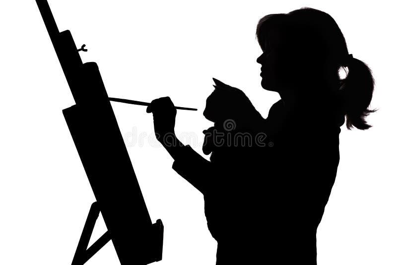 Silhouet van vrouw die een beeld op schildersezel, een profiel van een een borstel en kat van de meisjesholding in de handen, con stock afbeelding