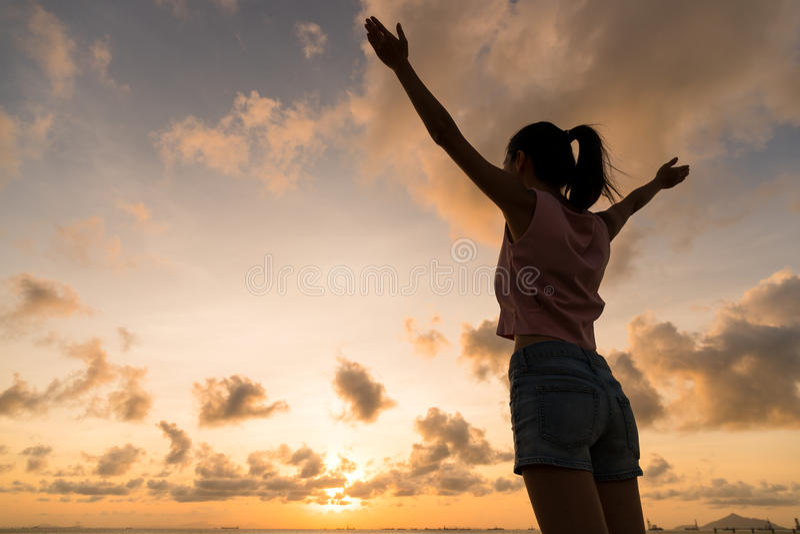 Silhouet van vrouw die hand opheffen omhoog onder zonsondergang royalty-vrije stock afbeeldingen