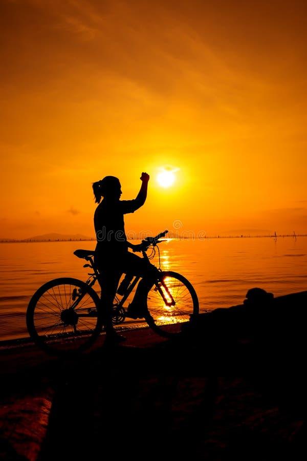 Silhouet van vrouw haar wapen omhoog naar de zon Suscessful peopl stock foto's