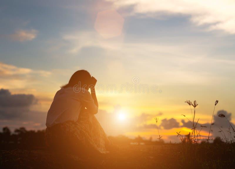 Silhouet van vrouw het bidden over mooie hemelachtergrond royalty-vrije stock afbeeldingen