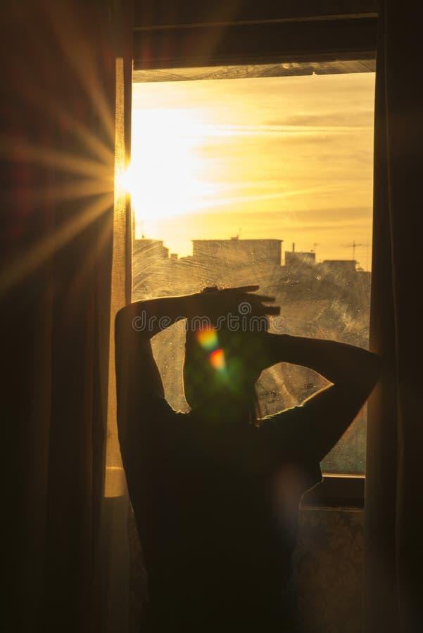 Silhouet van vrouw het kijken uit het venster backlight royalty-vrije stock foto's