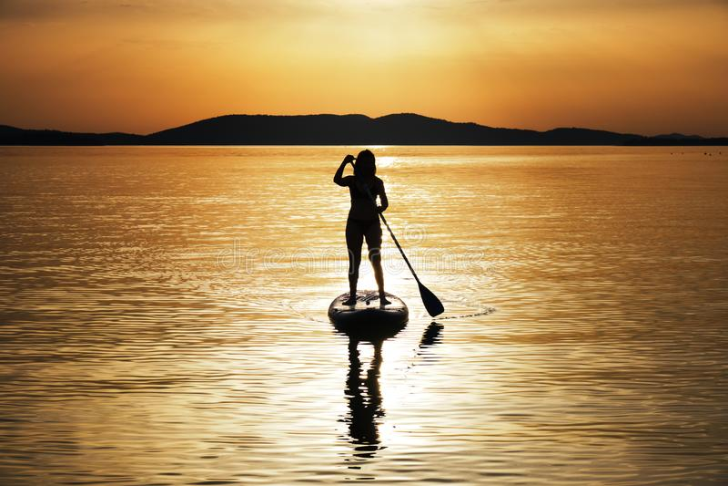 Silhouet van vrouw het paddelen bij zonsondergang op tribune omhoog paddleboard SUP in Kroatië, Adriatische Overzees, dichtbij Si royalty-vrije stock afbeeldingen