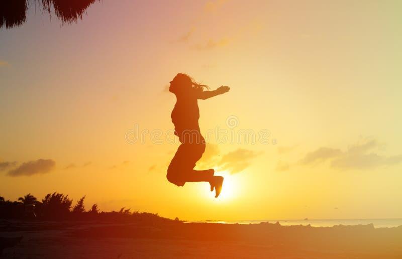 Silhouet van vrouw het springen bij zonsondergang royalty-vrije stock afbeelding