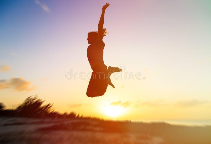 Silhouet van vrouw het springen op zonsondergang stock foto