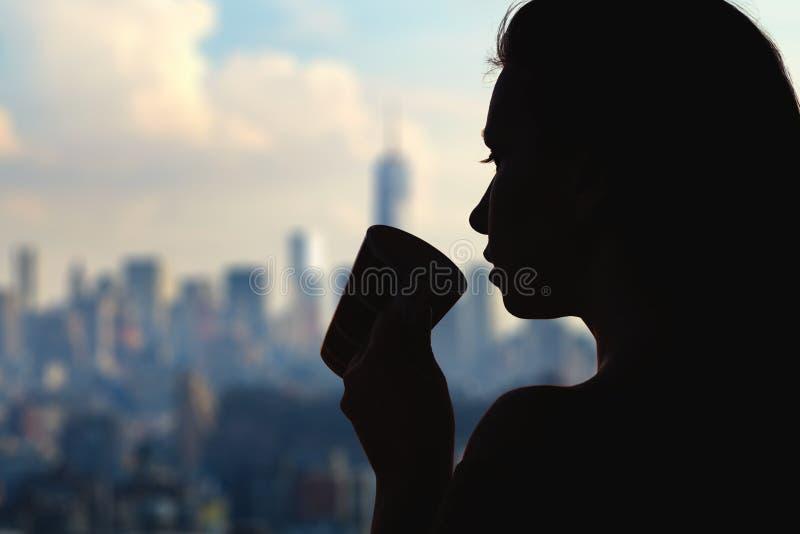 Silhouet van vrouw met kop van koffie op de de stadsachtergrond van New York stock foto's