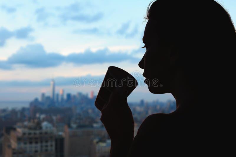 Silhouet van vrouw met kop van koffie op de de stadsachtergrond van New York royalty-vrije stock afbeeldingen