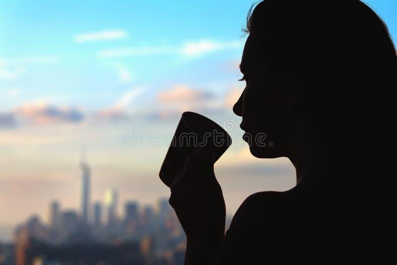 Silhouet van vrouw met kop van koffie op de de stadsachtergrond van New York royalty-vrije stock fotografie