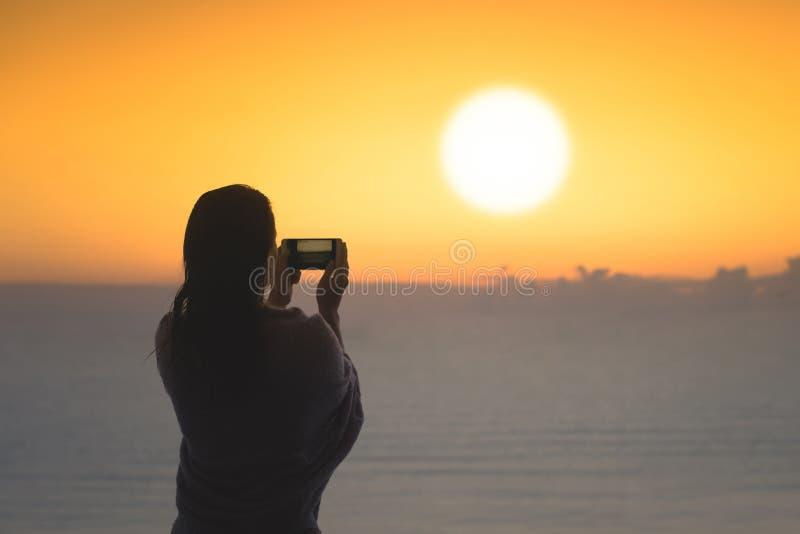 Silhouet van vrouw met nat die haar in een deken na het zwemmen wordt verpakt Vrouwelijk nemend beeld op mobiele telefoon die zic royalty-vrije stock afbeeldingen