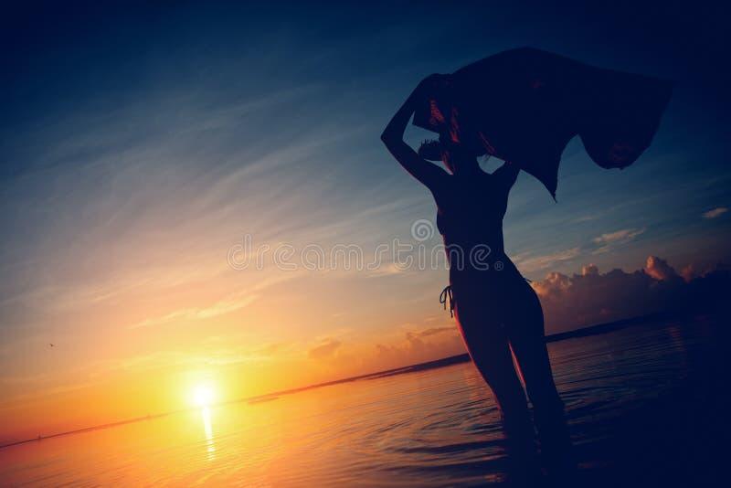 Silhouet van vrouw met sjaal die zonsondergang in de oceaan bekijken stock foto's