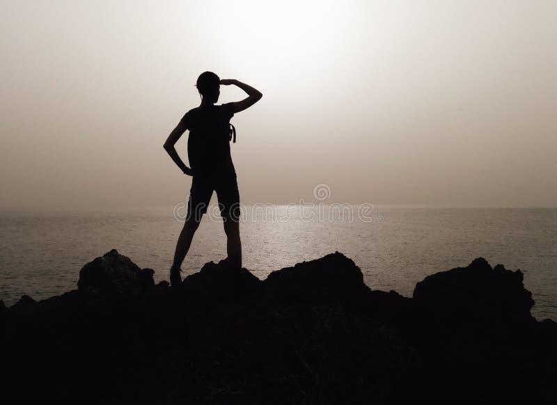 Silhouet van vrouw op een bovenkant van berg royalty-vrije stock afbeelding