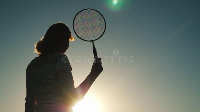 Silhouet van vrouw op middelbare leeftijd met tennisracket Actieve sporten, het concept van de de zomervakantie royalty-vrije stock afbeeldingen