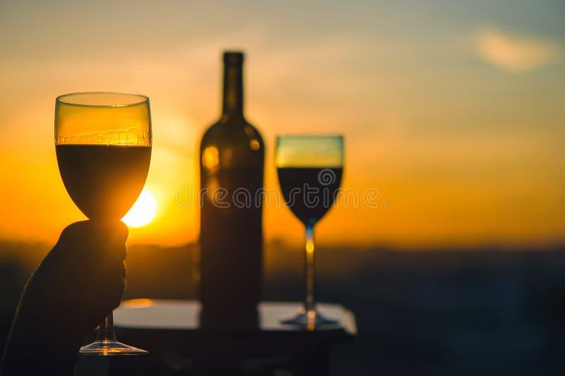 Silhouet van vrouwelijke hand roosterende wijn op zonsondergangachtergrond stock fotografie