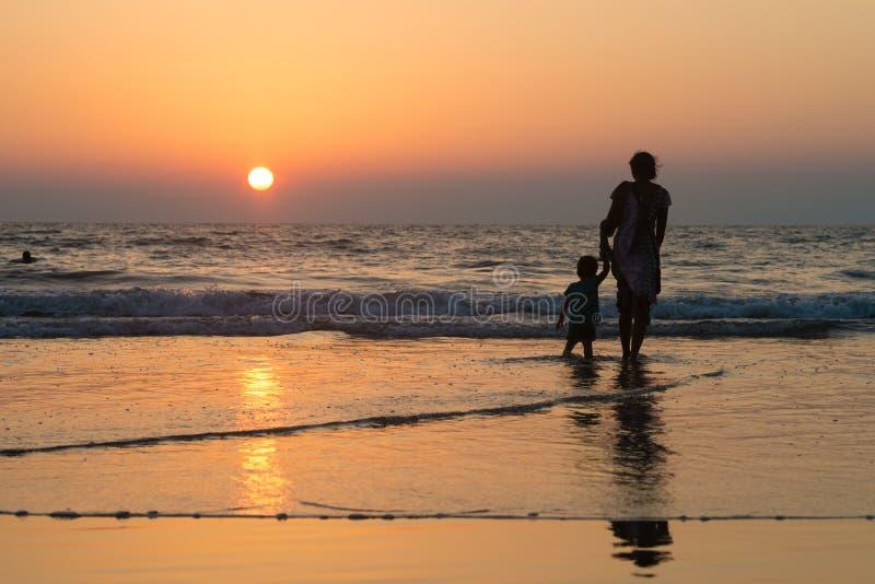 Silhouet van vrouwen met kind op het strand royalty-vrije stock fotografie