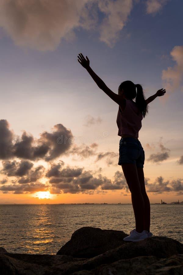 Silhouet van vrouwen open handen omhoog stock foto's