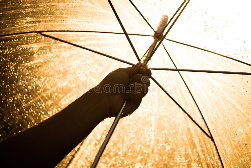 Silhouet van vrouwenhand die een paraplu in de regen openen royalty-vrije stock fotografie