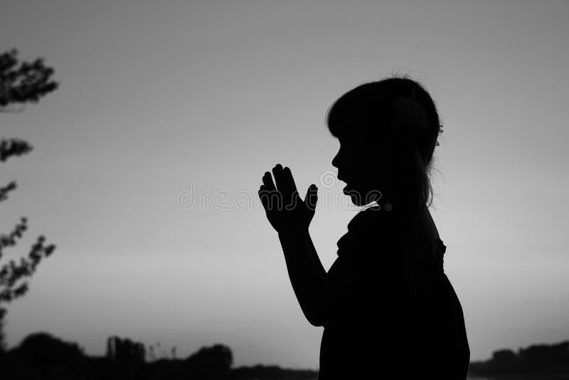 Silhouet van wat meisje het bidden stock foto