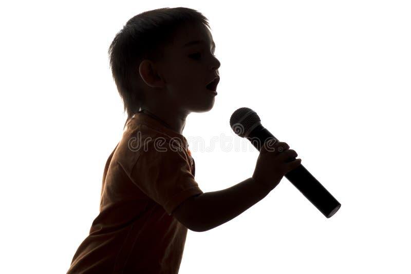 Silhouet van weinig gelukkige jongen die in microfoon zingen stock fotografie