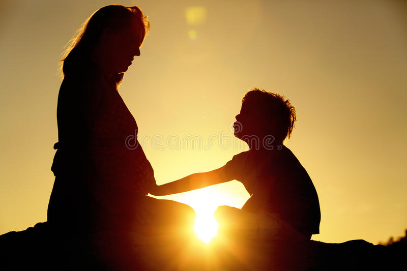 Silhouet van weinig jongen wat betreft zwangere moederbuik royalty-vrije stock afbeeldingen