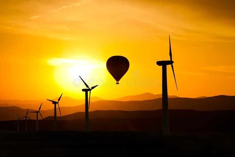 Silhouet van windturbines en van de hete luchtballon F bergen en de zonsondergang royalty-vrije stock afbeeldingen